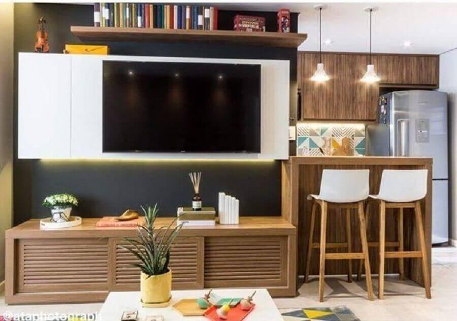 sala pequena com cozinha americana decorada com rack de madeira moderno Foto Duda Senna