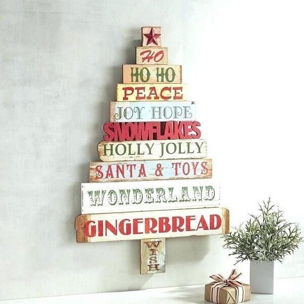 Árvore de Natal na parede feita com placas de madeira