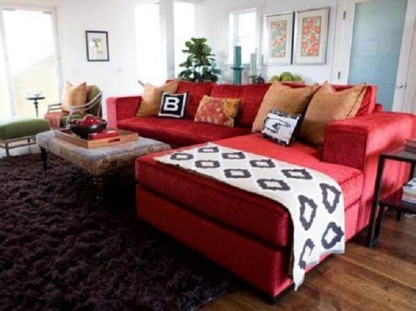 Sala de estar com sofá suede vermelho e tapete felpudo