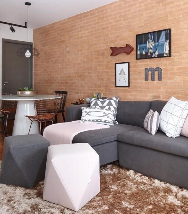 Sala de estar com parede de tijolinho aparente e sofá suede