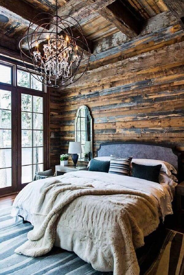 Quarto rústico de casal com lustre de ferro e parede de madeira
