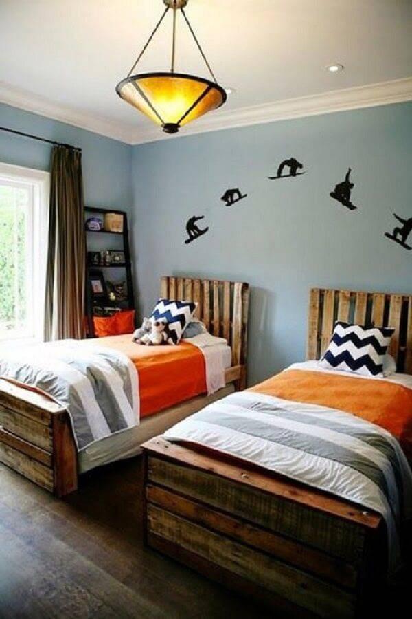 Quarto rústico compartilhado conta com camas de madeira e cabeceira de pallet