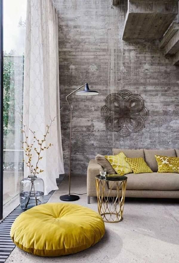 Sala de estar com pé direito alto e puff gigante em tom amarelo