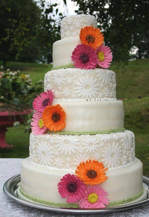 Bolo de festa decorado com fundo branco e flores de gérbera