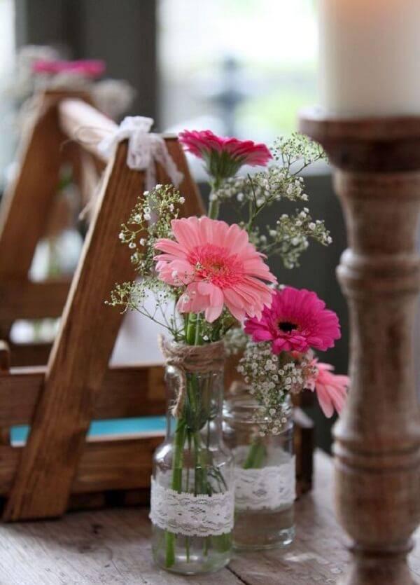 Vidraçaria com detalhes em renda recebem flores de gérbera em tom de rosa