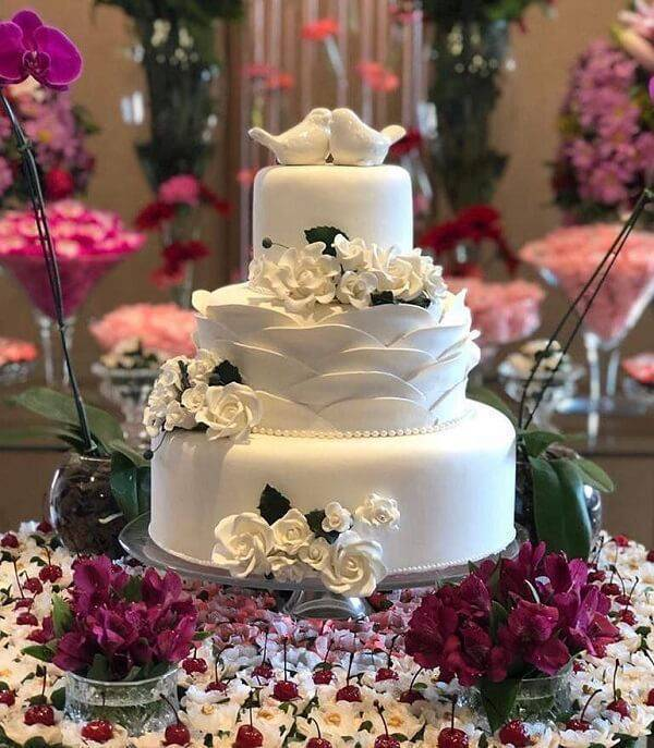 Fake cake made with flowers and porcelain birds finishing on top