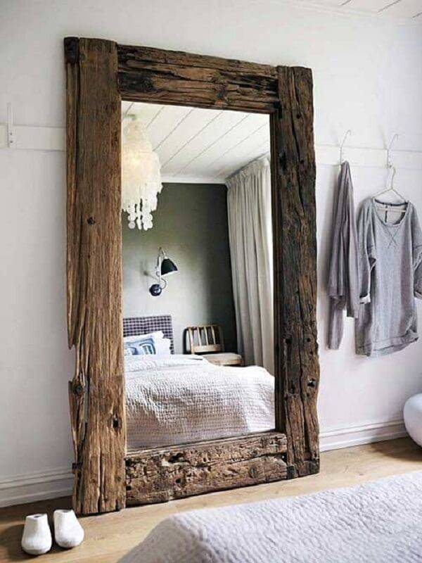 Espelho com moldura em madeira decora o quarto rústico