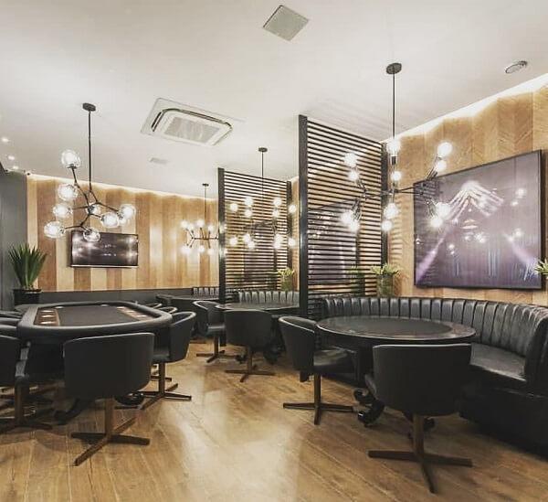 Estabelecimento comercial com mobiliário de couro preto e papel de parede neutro