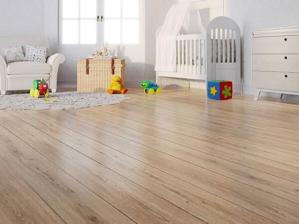 O quarto de bebê recebeu o acabamento com piso flutuante de madeira
