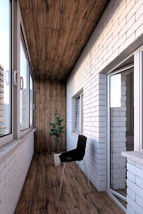 Varanda com parede de tijolinho branco e piso flutuante de madeira