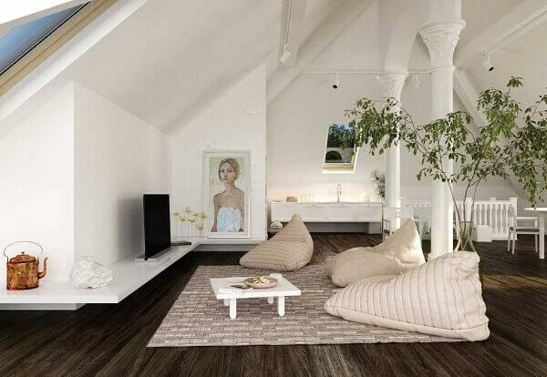 Piso laminado, puff gigante e decoração clássica na cor preta e branca complementa o estilo do sótão