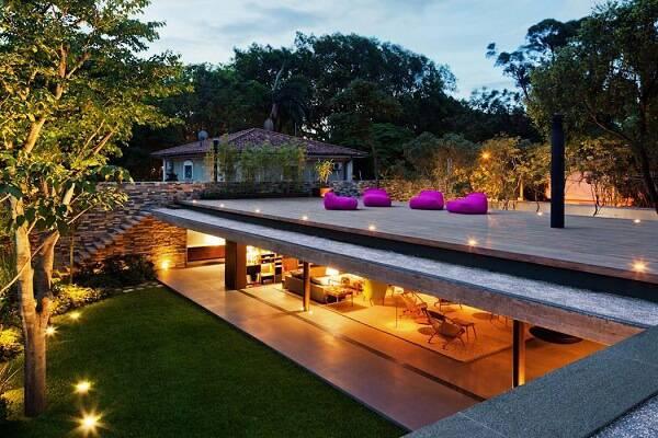 Puff rosa gigante, piso de madeira, gramado e iluminação
