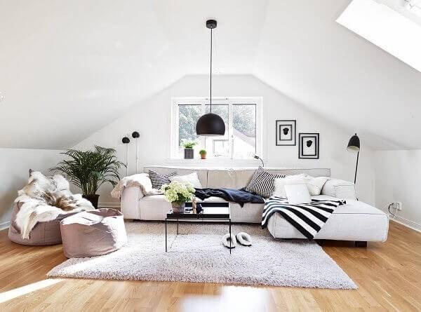 Sótão com decoração minimalista e puff gigante