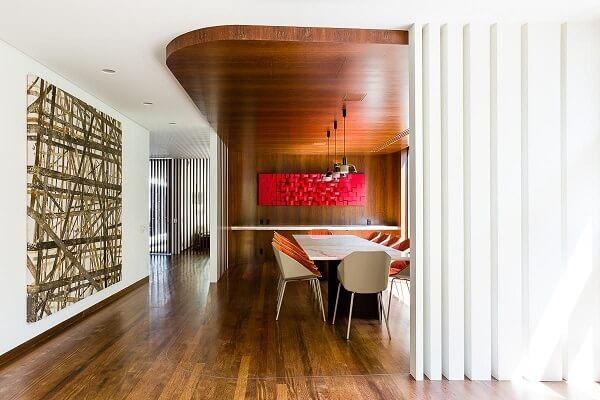 Sala de jantar com piso de madeira e quadro vermelho