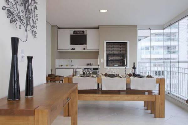 Varanda com churrasqueira com móveis de madeira