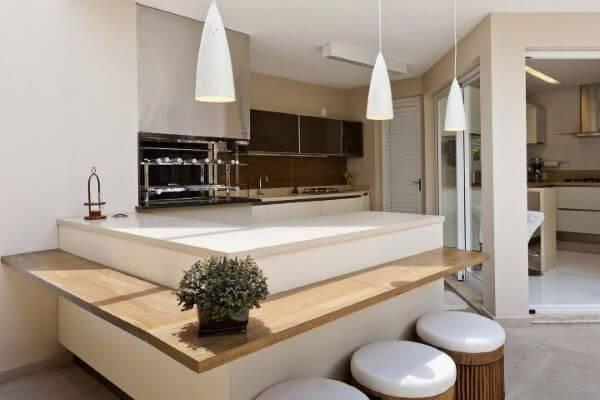 Varanda com churrasqueira pequena branca com balcão de madeira
