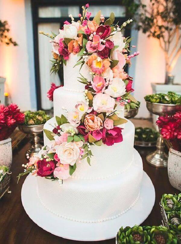 Bolo de casamento fake com fundo branco e cascata de flores naturais