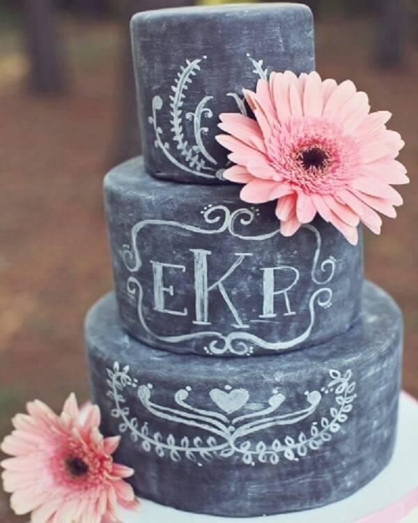 Bolo fake lousa com fundo preto e acabamento feito com flor de gérbera rosa