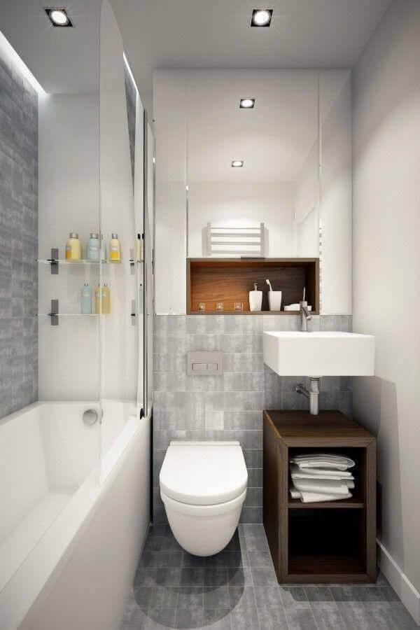 banheiro pequeno planejado cinza e branco com gabinete pequeno de madeira Foto Divian Arts