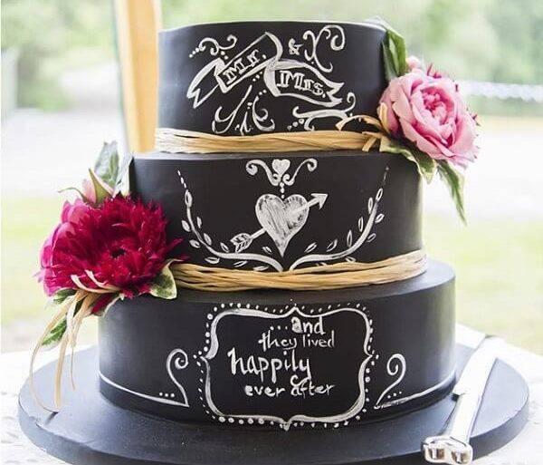 Bolo fake casamento com fundo preto, frases e flores nas laterais