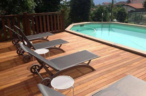 Borda de piscina de madeira com deck e espreguiçadeiras