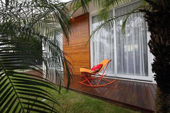 cor laranja - parede com tacos de madeira e cadeira metálica