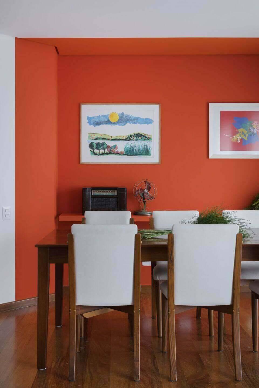 cor laranja - parede laranja, mesa de madeira e prateleira