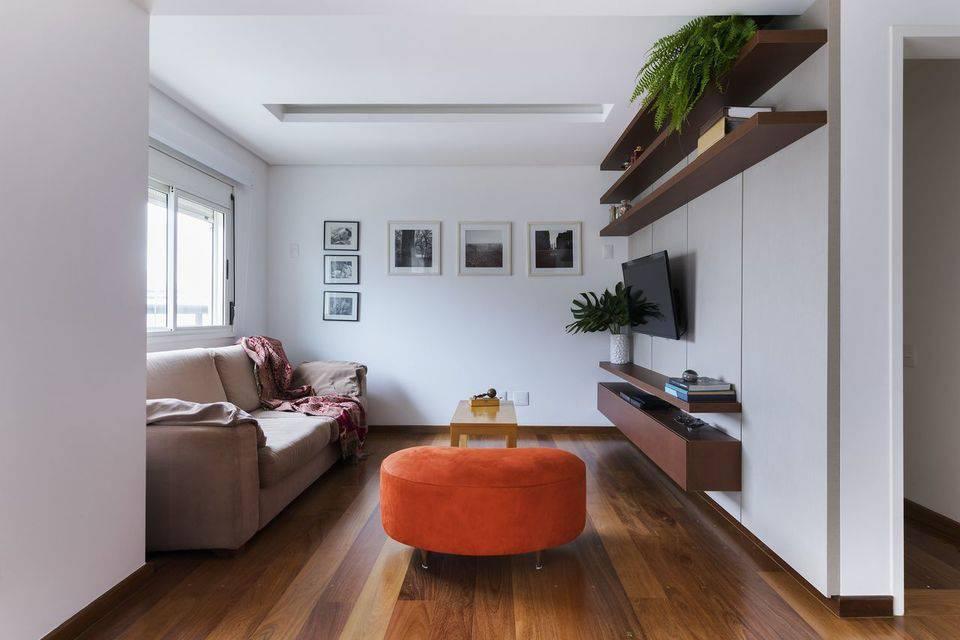 cor laranja - puff de tecido laranja, piso de madeira e rack