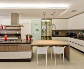 cozinha americana grande com mesa de madeira ligada a bancada  Foto Cíntia Mara Petronetto