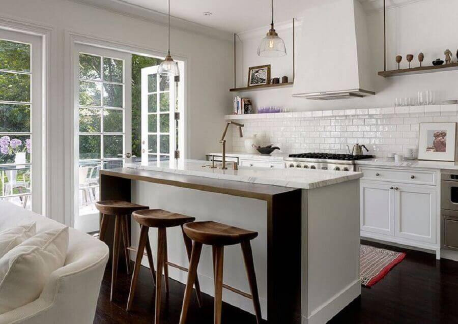 cozinha com ilha e bancada de madeira integrada com a sala Foto Homedit