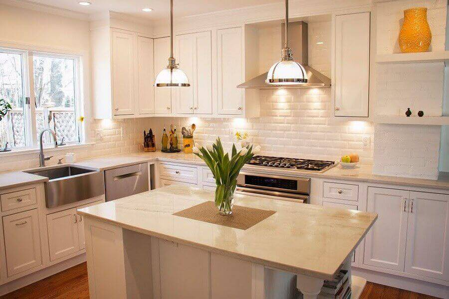 cozinha com ilha pequena e parede de tijolinho branco  Foto Decorando