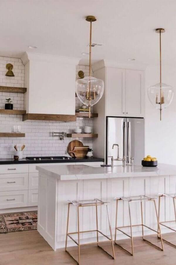 cozinha com ilha toda branca decorada com parede de tijolinho e banquetas minimalistas  Foto Minimal Kitchen