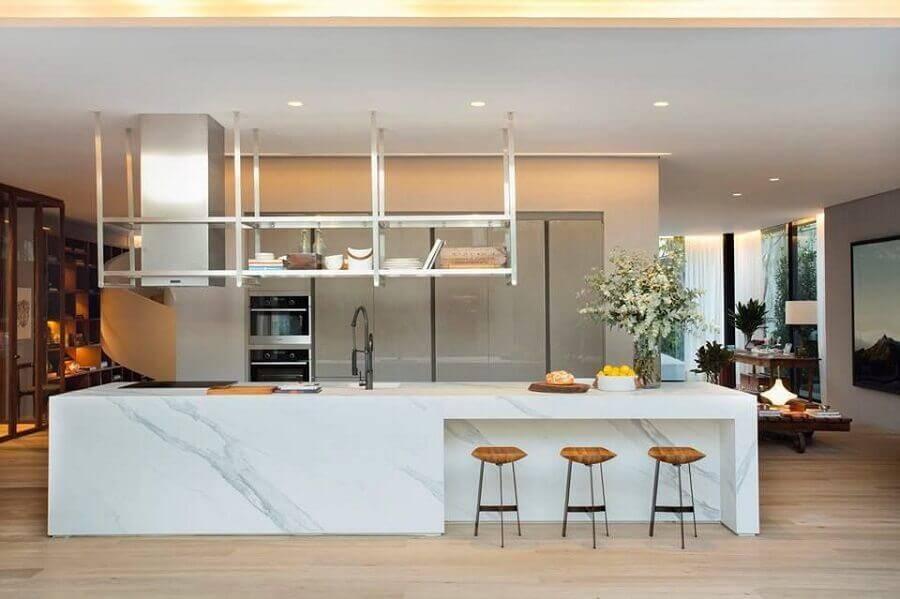 cozinha conceito aberto com ilha de mármore decorada com banquetas de madeira Foto Cosentino