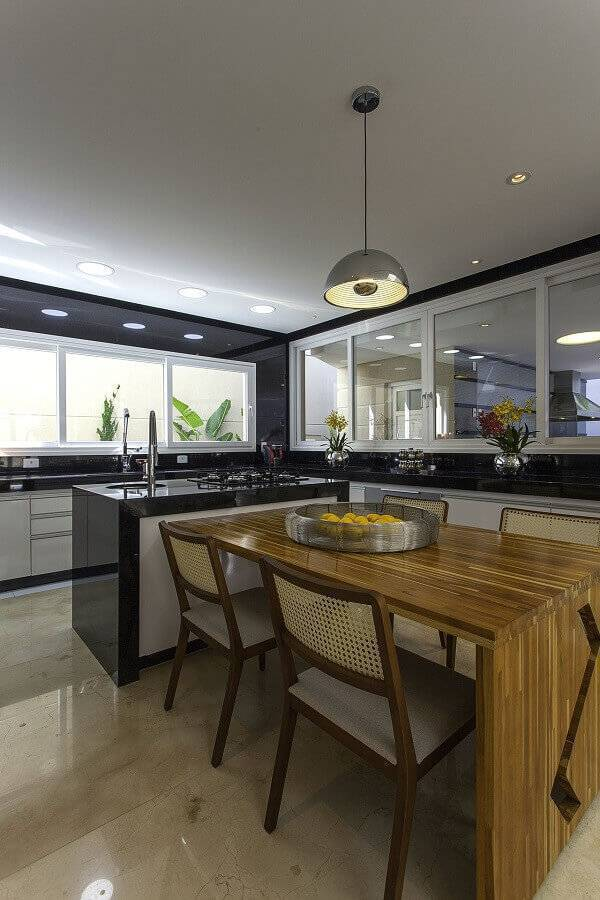 cozinha planejada com ilha com cooktop e mesa de madeira Foto Iara Kilaris