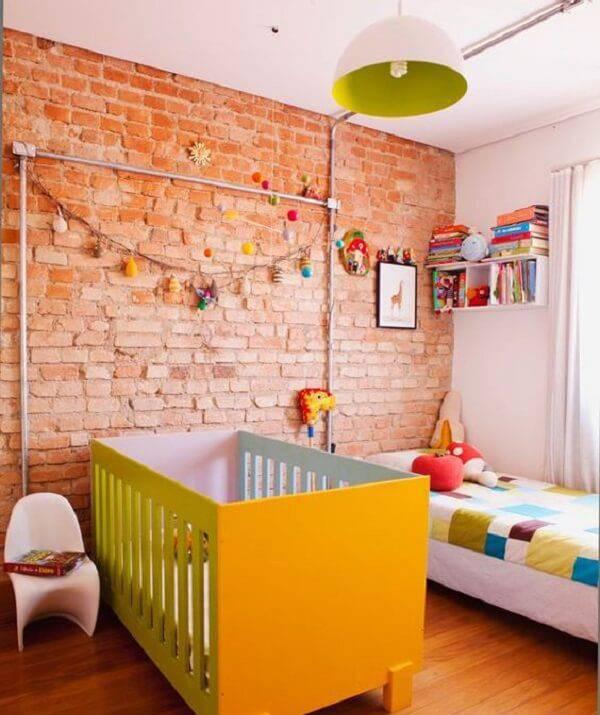 Quarto de bebê rústico com parede de tijolinho e berço amarelo