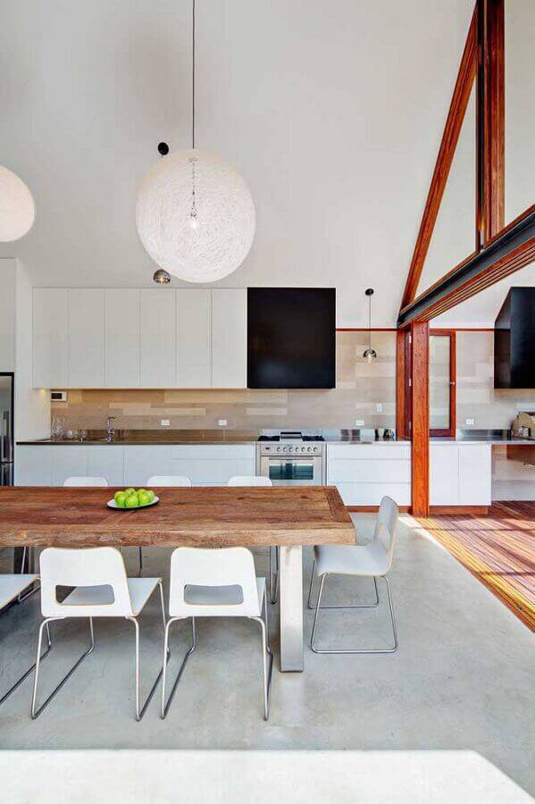decoração com mesa de madeira rústica e armário de cozinha grande toda branca Foto Behance