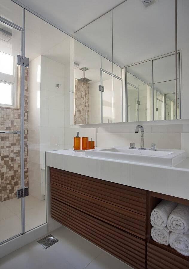 decoração para banheiro pequeno planejado com pastilhas na área do box e armário de madeira Foto Da. Hora