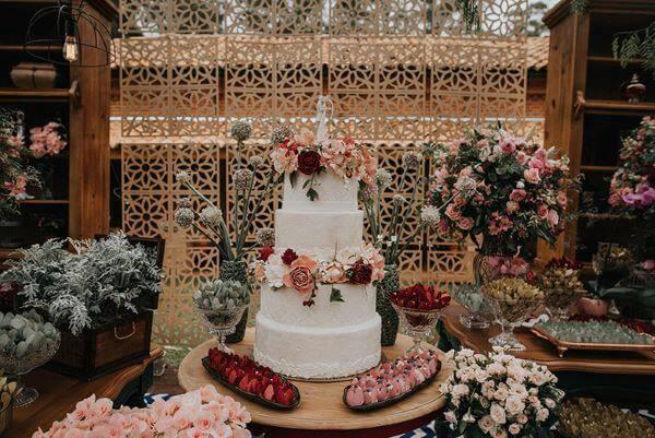 Decoração com folhagens na mesa de bolo de casamento