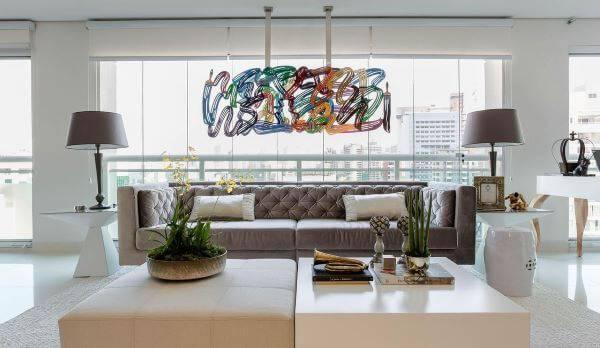 Sala de estar com cores neutras e lustre colorido