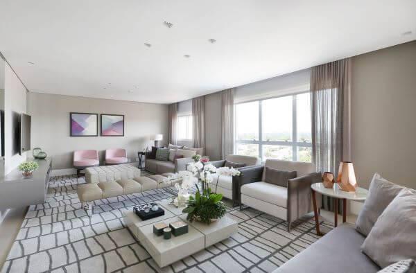 Decoração de sala de estar com tapete claro e poltronas de cores neutras