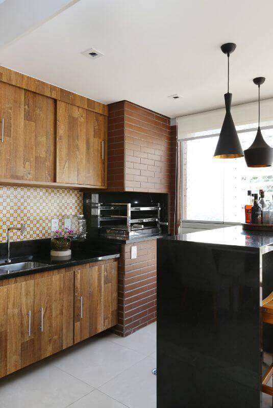 Varanda com churrasqueira de tijolinhos e armários de madeira