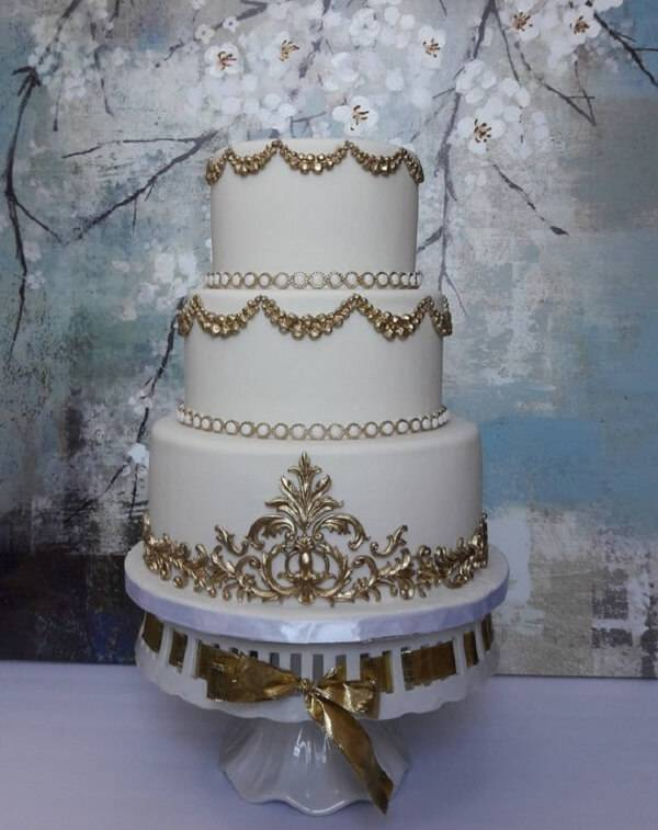 Modelo fake de bolo com detalhes em dourado