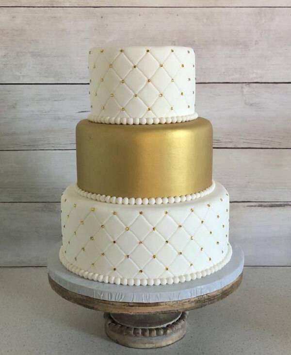 Modelo fake de bolo em tons de branco e dourado