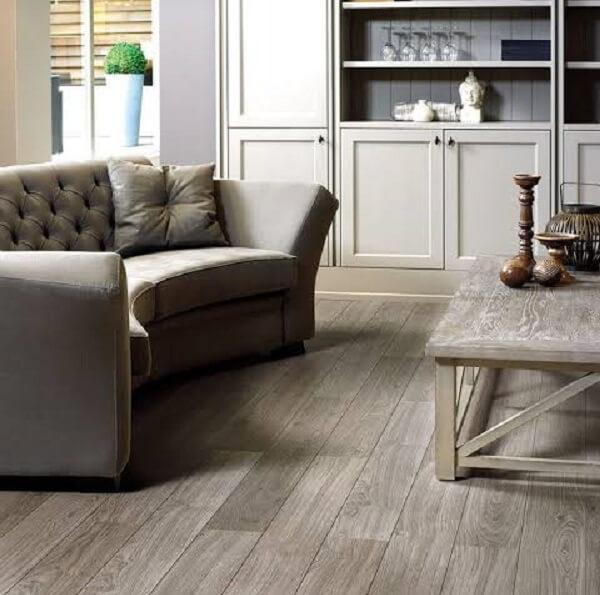 Sofá meia lua e piso flutuante de madeira para sala de estar