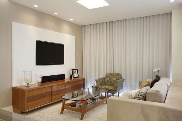 Poltrona para sala de tv com tecido estampado se mistura com o sofá neutro