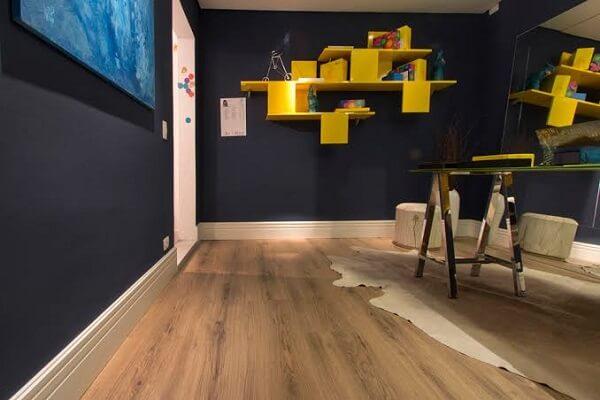 Quarto com prateleiras amarelas e piso flutuante