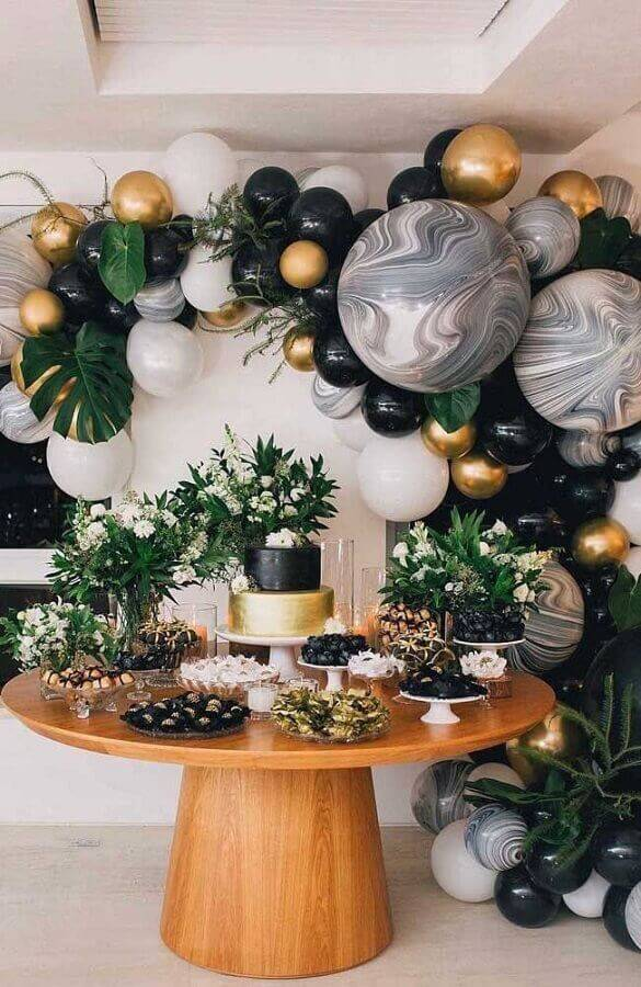 mesa de aniversário adulto com detalhes dourados e bolas pretas  Foto Pinosy