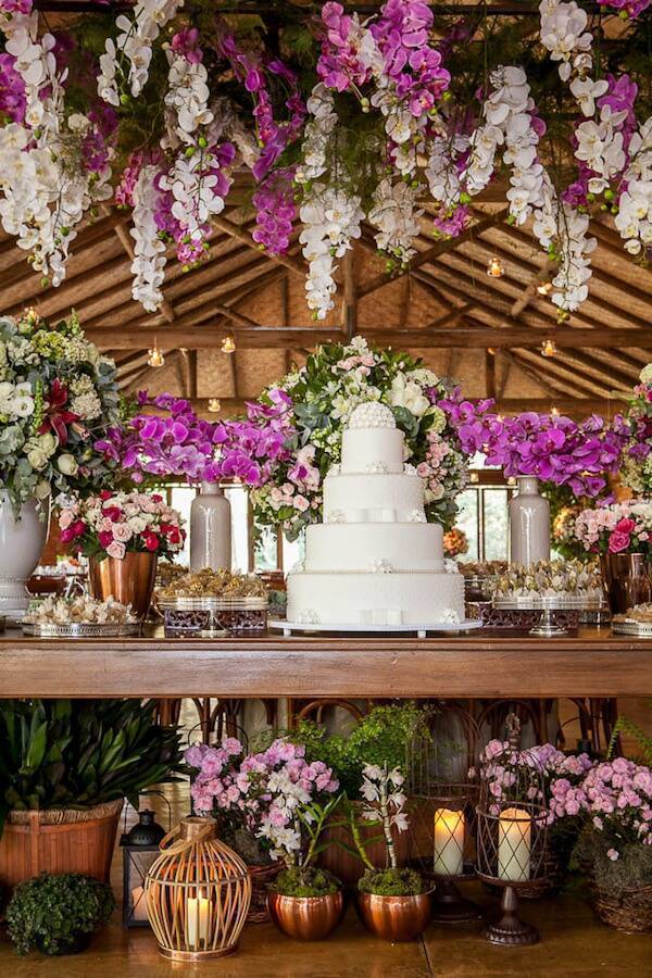 Mesa de bolo de casamento com orquídeas roxas e brancas