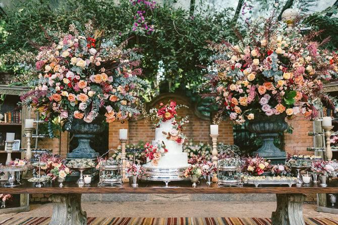 Mesa de bolo de casamento boho chic com arranjos coloridos