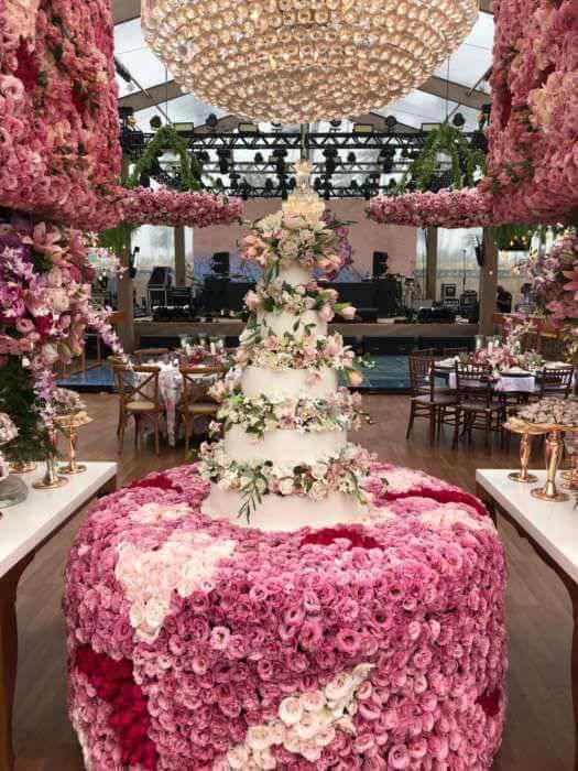 Mesa de bolo de casamento com flores combinando com a decoração